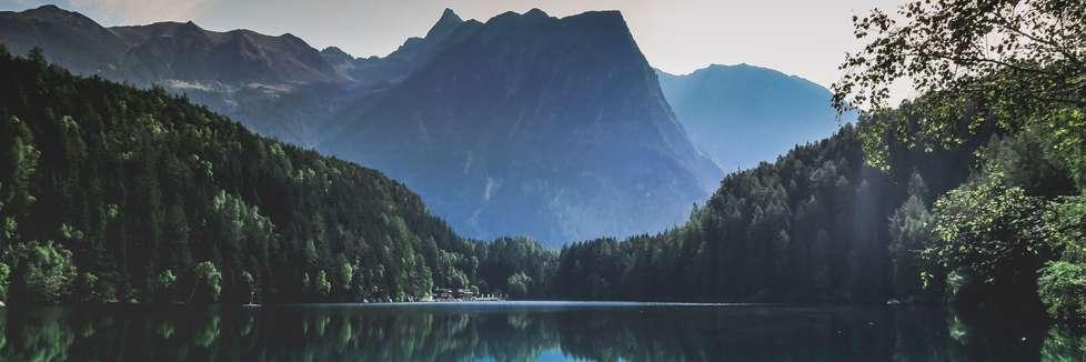 Blick auf einen See in Österreich. Im Hintergrund ist ein hoher Berg zu sehen.